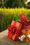 Caja de regalo de la Navidad con las decoraciones en la tabla de madera en puesta del sol del campo Foto de archivo libre de regalías