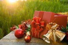 Caja de regalo de la Navidad con las decoraciones en la tabla de madera en puesta del sol del campo Fotos de archivo libres de regalías