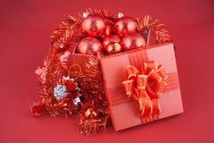 Caja de regalo de la Navidad con las decoraciones y bola del color en fondo rojo Imagen de archivo libre de regalías
