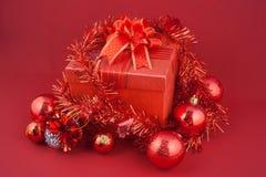 Caja de regalo de la Navidad con las decoraciones y bola del color en fondo rojo Fotos de archivo