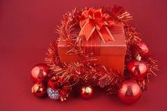 Caja de regalo de la Navidad con las decoraciones y bola del color en fondo rojo Fotografía de archivo
