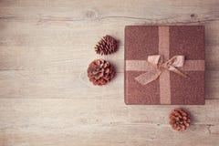 Caja de regalo de la Navidad con maíz del pino en fondo de madera Visión desde arriba Fotografía de archivo libre de regalías