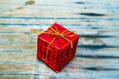 Caja de regalo de la Navidad en el follaje que envuelve con el arco del hilo del oro Fotografía de archivo libre de regalías