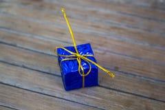 Caja de regalo de la Navidad en el follaje que envuelve con el arco del hilo del oro Fotos de archivo
