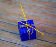 Caja de regalo de la Navidad en el follaje que envuelve con el arco del hilo del oro Fotografía de archivo