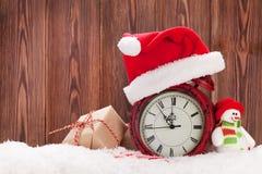 Caja de regalo de la Navidad, muñeco de nieve y despertador Fotos de archivo