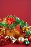 Caja de regalo de la Navidad y de la Feliz Año Nuevo con las decoraciones y bola del color aislada en fondo rojo Fotos de archivo