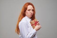 Caja de regalo de ocultación adolescente del pelo rojo codicioso con un presente Foto de archivo libre de regalías