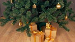 Caja de regalo debajo del árbol de abeto verde de la Navidad La caja de regalo de Brown se coloca en el piso Día de fiesta de la  almacen de metraje de vídeo