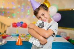 Caja de regalo del abarcamiento del muchacho durante fiesta de cumpleaños en casa Imágenes de archivo libres de regalías