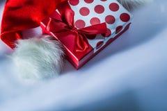 Caja de regalo del casquillo de Santa Claus en la superficie blanca foto de archivo