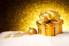 Caja de regalo del oro de la Navidad con las bolas y estrella en nieve Imagen de archivo libre de regalías