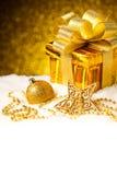 Caja de regalo del oro de la Navidad con las bolas y estrella en nieve Fotos de archivo libres de regalías