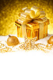 Caja de regalo del oro de la Navidad con las bolas y estrella en nieve Fotografía de archivo libre de regalías