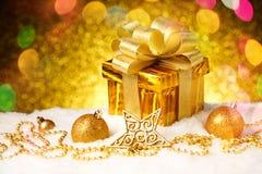 Caja de regalo del oro de la Navidad con las bolas y estrella en nieve Fotos de archivo