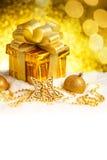 Caja de regalo del oro de la Navidad con las bolas y estrella en nieve Imagenes de archivo