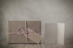 Caja de regalo del papel de Brown con la tarjeta rosada de la rafia y de felicitación Fotos de archivo