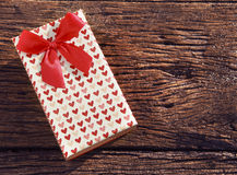 Caja de regalo del presente del punto del corazón con la cinta roja en vieja textura de madera Foto de archivo libre de regalías
