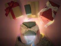 Caja de regalo del verde del control de la mano del ` s de la muchacha de la belleza con el paño del invierno, luz Imagen de archivo libre de regalías