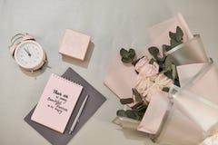 Caja de regalo, despertador y flores color de rosa rosadas Tarjeta de felicitaci?n para el d?a de la madre o de la mujer foto de archivo libre de regalías