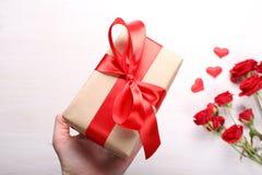 Caja de regalo a disposición y rosas rojas Imagenes de archivo