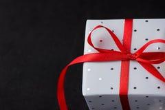 Caja de regalo elegante envuelta en Grey Silver Paper con la polca Dots Red Ribbon en fondo negro Tarjeta del día de San Valentín Fotos de archivo
