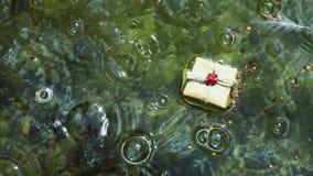 Caja de regalo en el agua almacen de video