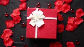 Caja de regalo en la tabla de piedra negra Fondo romántico del día de fiesta con los pétalos color de rosa