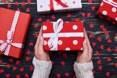 Caja de regalo en las manos de la mujer aisladas sobre la disposición plana del grunge Imagen de archivo libre de regalías