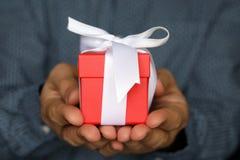 Caja de regalo en las manos masculinas cerca para arriba fotografía de archivo libre de regalías