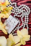 Caja de regalo en un fondo de orquídeas amarillas foto de archivo libre de regalías