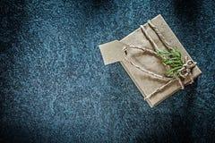 Caja de regalo envuelta con la rama del thuya en días de fiesta negros del fondo foto de archivo