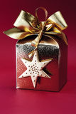 Caja de regalo envuelta de oro con el arco contra fondo rojo Imagen de archivo