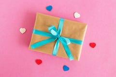 Caja de regalo envuelta del papel del arte y de la cinta azul con los corazones coloridos en el fondo rosado imágenes de archivo libres de regalías
