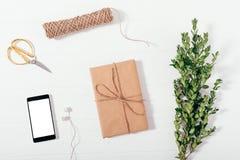 Caja de regalo envuelta en papel marrón cerca de las tijeras del oro foto de archivo