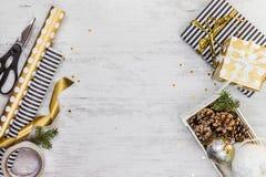 Caja de regalo envuelta en papel rayado blanco y negro con la cinta de oro, un cajón por completo de conos del pino y de juguetes Imagen de archivo libre de regalías