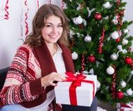 Caja de regalo feliz de la abertura de la mujer joven cerca del árbol de navidad Fotografía de archivo libre de regalías