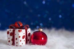 Caja de regalo festiva con la bola roja de la Navidad en backgroun azul del bokeh Imagen de archivo libre de regalías