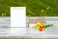 Caja de regalo, flores y marco blanco del vintage con el lugar para su te fotografía de archivo
