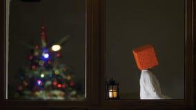 Caja de regalo graciosamente del arreglo del niño en su calor, lámpara en la ventana, árbol de navidad en la niñez del fondo, jug metrajes