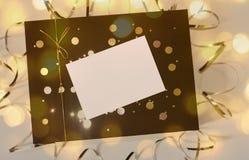Caja de regalo hermosa con la cinta y el arco de oro y tarjeta vacía para el texto imagenes de archivo