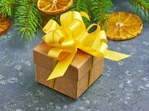 Caja de regalo de Kraft de la Navidad con el arco amarillo en un backgro de piedra gris Foto de archivo