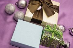 Caja de regalo de la Navidad con las decoraciones en fondo rosado Foto de archivo