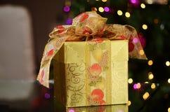 Caja de regalo de la Navidad con las luces y árbol en el fondo Fotografía de archivo libre de regalías