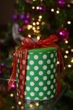 Caja de regalo de la Navidad con las luces y árbol en el fondo Fotografía de archivo