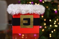 Caja de regalo de la Navidad con las luces y árbol en el fondo Imagen de archivo