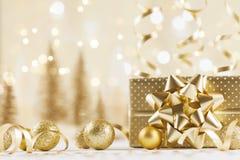 Caja de regalo de la Navidad contra fondo de oro del bokeh Tarjeta de felicitación del día de fiesta fotografía de archivo libre de regalías