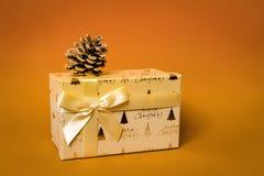 Caja de regalo de la Navidad en fondo anaranjado imagenes de archivo