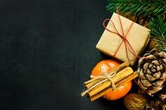 Caja de regalo de la Navidad en nueces de los conos del pino de las ramas de árbol de abeto de los palillos de canela de la manda Imagen de archivo