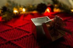 Caja de regalo de la Navidad en scraf rojo con las luces Imagen de archivo libre de regalías